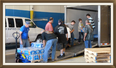 Bikers for Jesus help with unloaded cases of water.