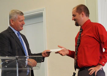 Paul Hoover, President of Upper Columbia Conference, hands the Grant of $15,000 check to Pr. Dayv Lounsbury of Spokane Central SDA Church.Photo Credit: Art Lenz