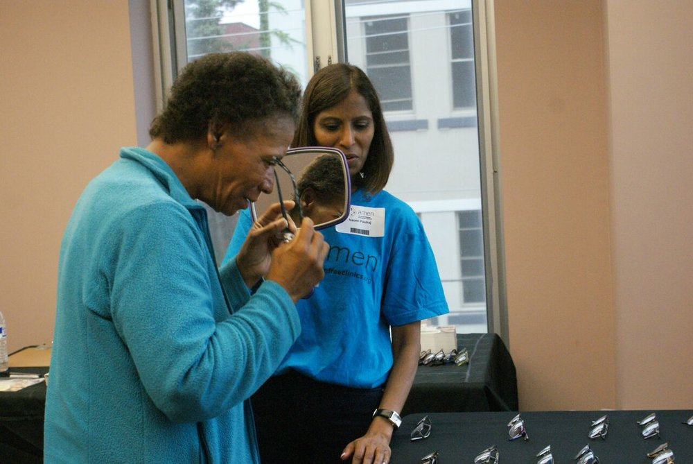 Maryland volunteer, Naomi Paulraj, helps a patient choose the frame for her glasses. Photo by Kenneth Moore, Jr.