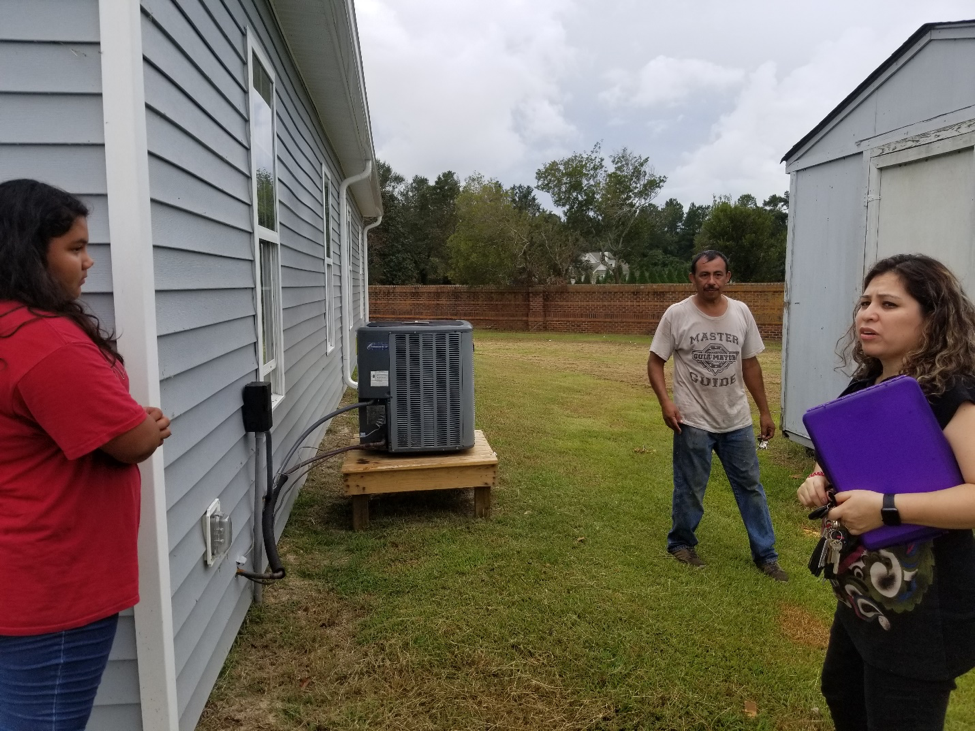 ACS Director and local elder show how water came above the air-conditioning unit of the Spanish SDA Church of New Bern.