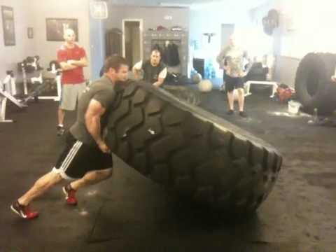 Rob Orlando flipping a 1,000lbs tire.  When picking up a tire you apply a driving force. The movement is more similar to a push off the ground than a pull off the ground.