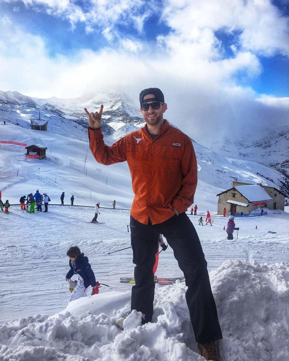 Skyline athlete Ryan Bailey hook em horns in Switzerland.