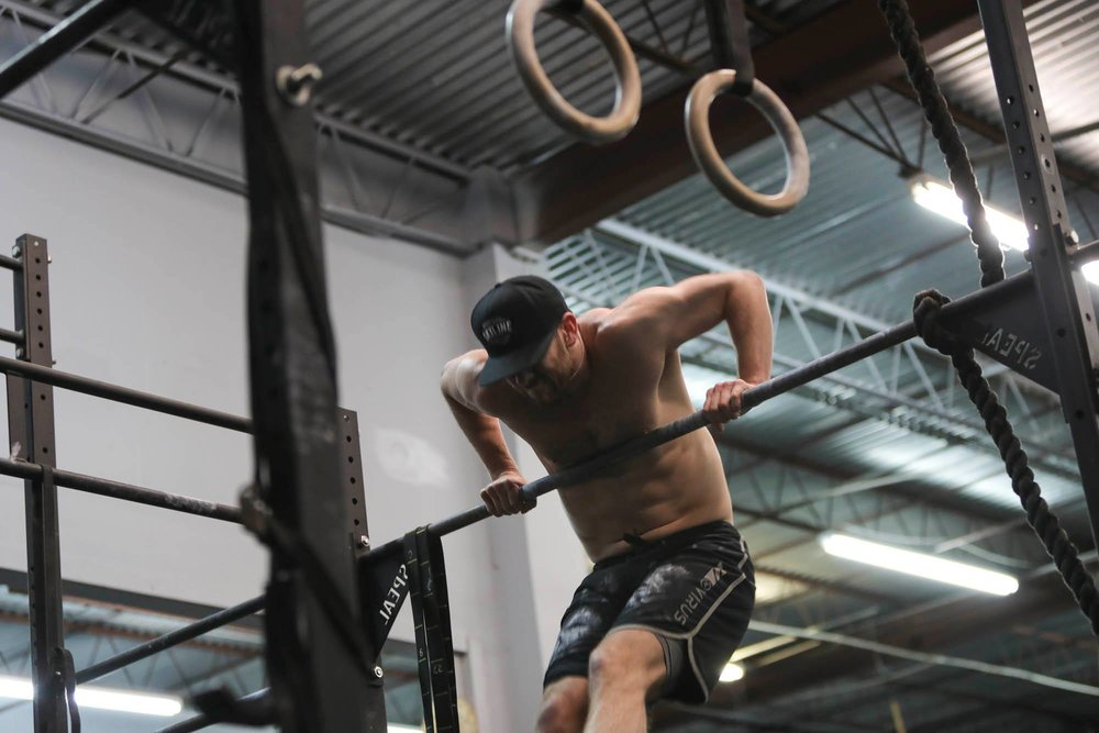 Ryan Bailey performing bar muscle ups.  As fatigue sets in you will start catching really low on the bar as Ryan shows in this picture.  Ryan is doing a good job of keeping his elbows over his hands to help him stay above the bar.