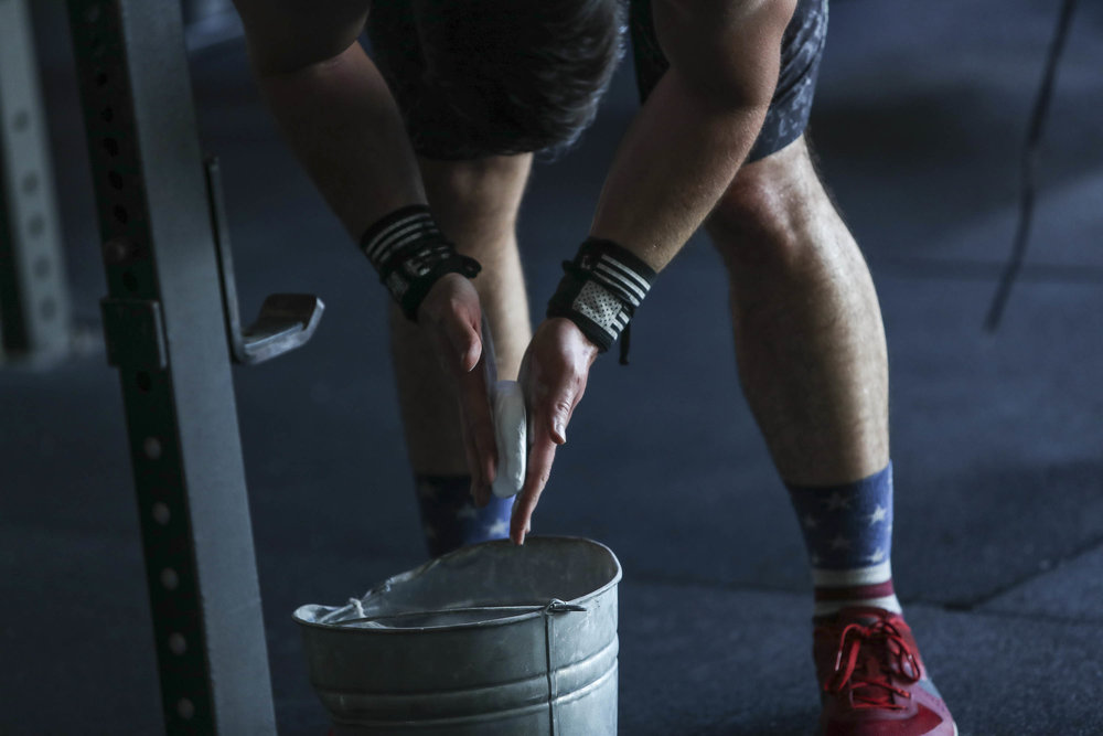 Ryan Kealler showing the proper way to chalk your hands. You put your hands in bucket, chalk while hands are still in bucket. Clap away excess over bucket, then go lift some shit.