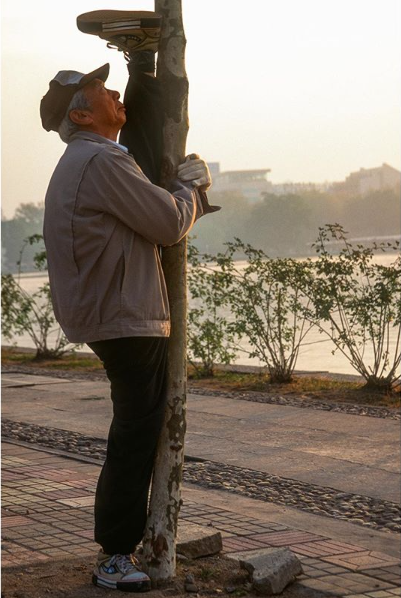 "Instagram post from National Geographic:   ""Morning stretch at West Lake in Hangzhou: In China it is common to see elderly people practicing Tai Chi, exercising, and stretching in parks around the country. In fact, most have not exercised seriously until after retirement, but something tells me stretching is not new to this silver-haired gentleman.""  Photograph by Michael Yamashita"