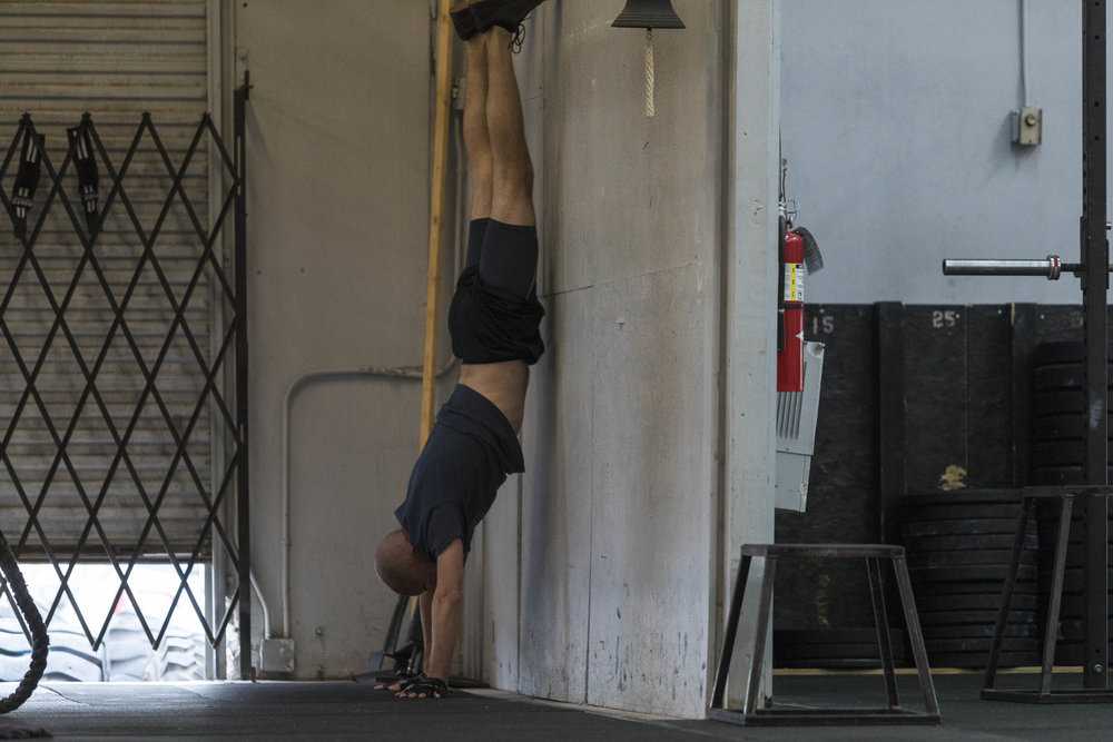 Cyril scaling handstand walks with wall walks. Wall walks are the best way to build the strength to prepare us for handstands and handstand walks. This also helps us get more accustom to being upside down.