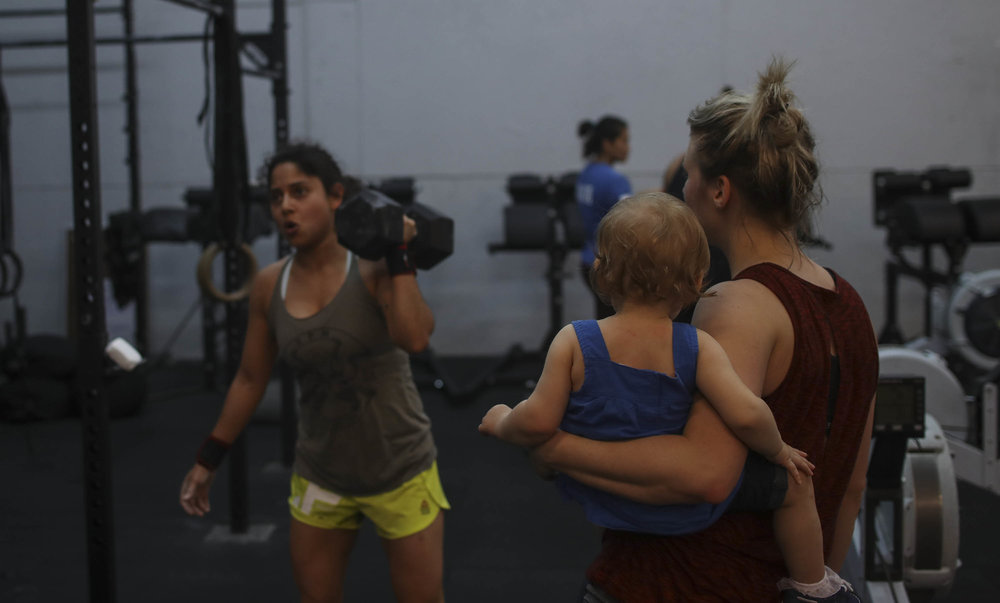 Anna with a one arm dumbbell press.  Being watched carefully by Adlee and Amisha.