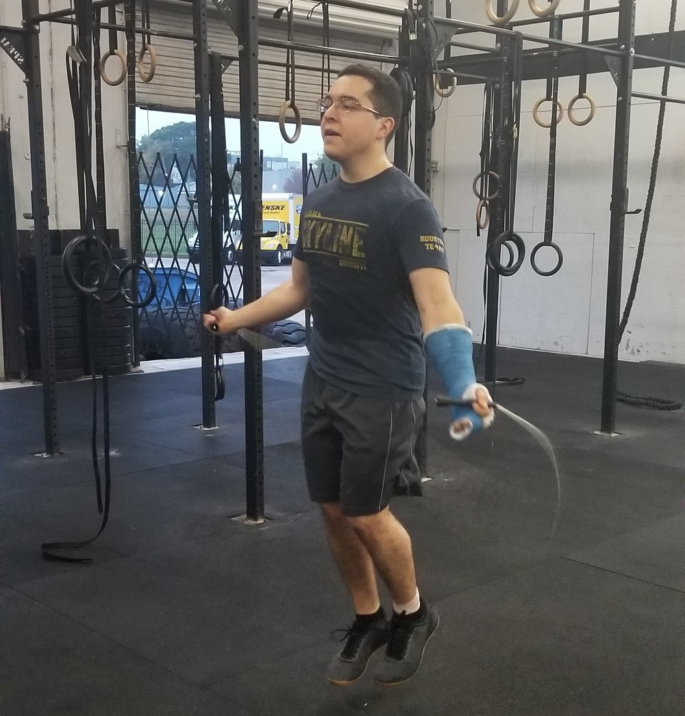 Christian Carrion a avid 6am goer that recently broke his hand.  He doesn't let this stop him from coming to class and scaling the workout to his ability. Double-unders are a little tricky with a cast so Christian is seen here scaling with single-unders. Scalability is our expertise, don't let injuries stop your routine, talk to the coach and we will get you moving in no time!