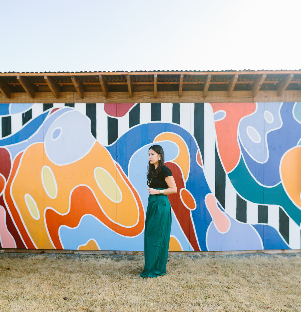 Living life creatively - Woman in black top, green skirt, turquoise cuff bracelet and brass, gold and round brass dot earrings outside in front of colorful wall