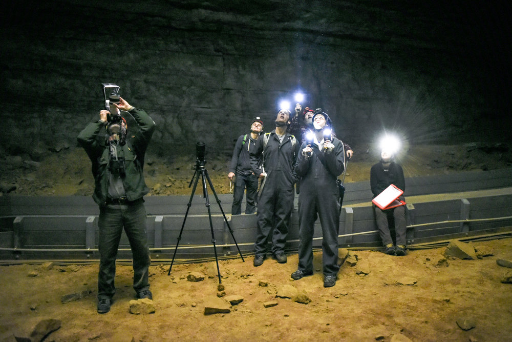 Thomas, left, photographs a bat hibernating on the ceiling of the Historic Entrance section of Mammoth Cave.