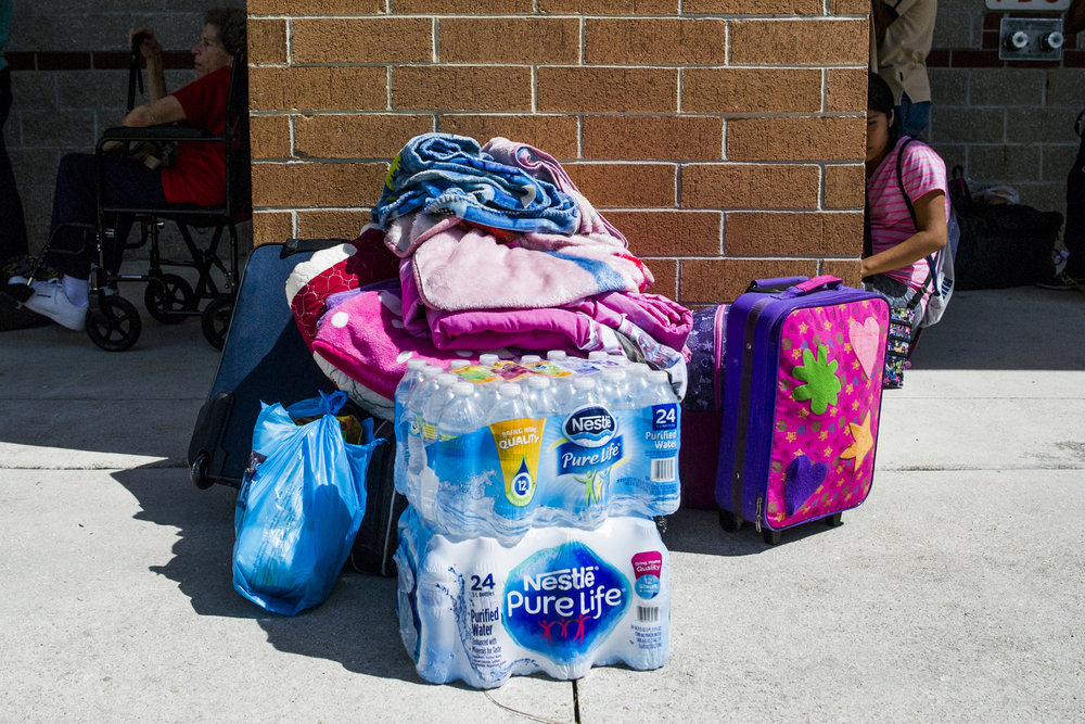 A family's supplies sit outside of Gulf Coast High School, a hurricane shelter.
