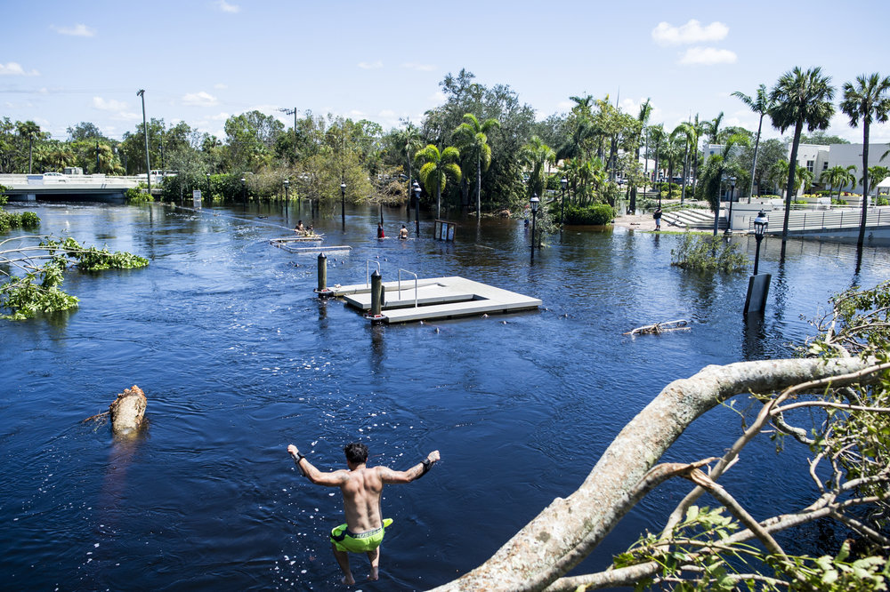 Pedro Mendez jumps into the flooded Imperial River after Hurricane Irma in Bonita Springs