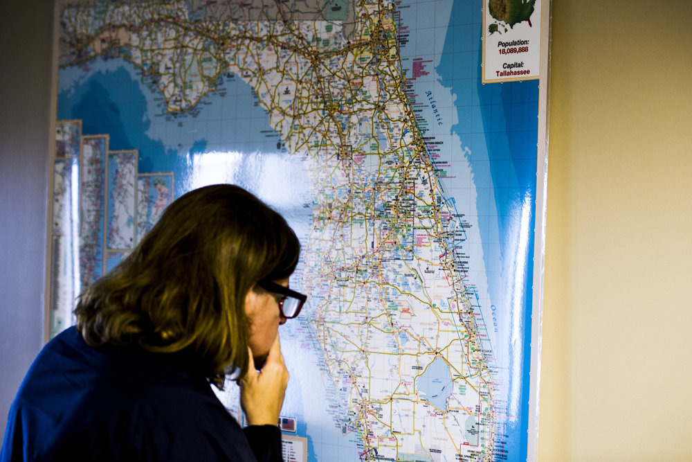 A FEMA employee studies a map of Florida at the Collier County Emergency Services Center.