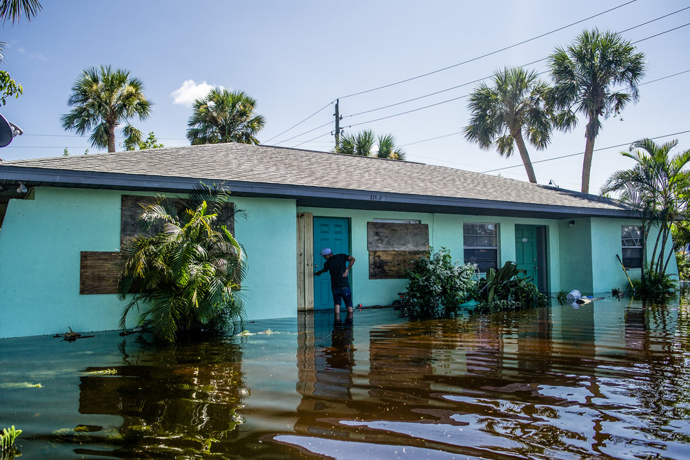 Roberto Abram Pu Imul closes the door to his flooded home in Bonita Springs.