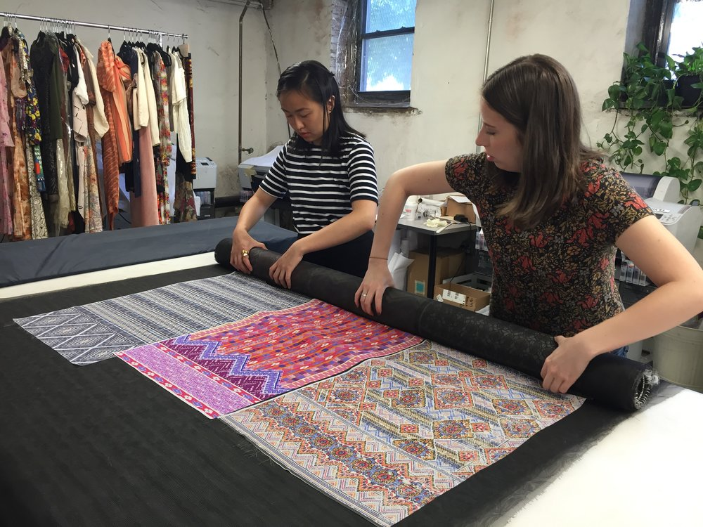 Tiffany Lin (left) and production assistant Paige (right) roll up printed fabric samples of original Printfresh designs, preparing them to be put in the industrial steamer.