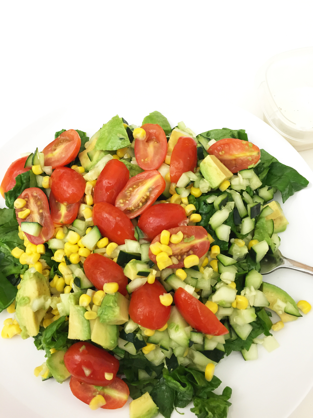 Tomatoes, cucumber, corn, avocado, spinach. Ranch on the side.