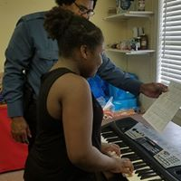 Mr. Pat, Music Instructor teaching Madison how to read and play music.