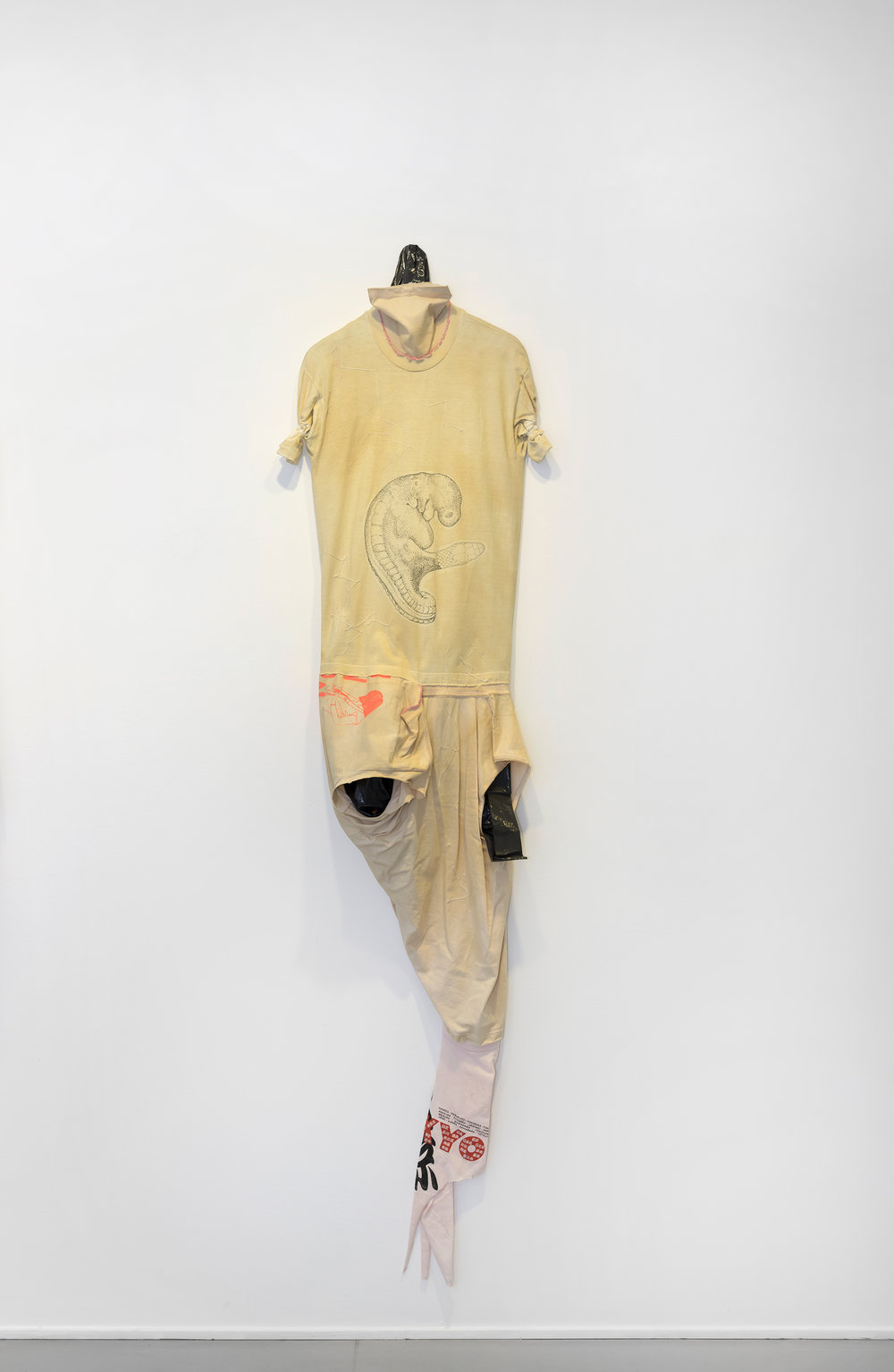 Leif Holmstrand,  Costume for a New Tail (It's a Girl)  (2015), textile wall sculpture: T-shirt fabric, print depicting human fetus plus snake head, garbage bag plastic, pearls et cetera. Foto: Øystein Thorvaldsen