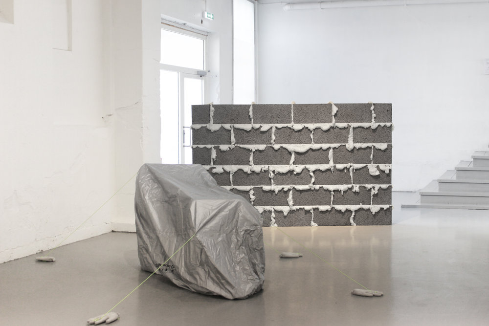 Untitled , 2018, dimensions variable, (motorcycle cover, cement hands, ropes).  Wall , 2018, 250 cm x 170 cm, ( bricks, expanded foam). Foto: Audun Alvestad