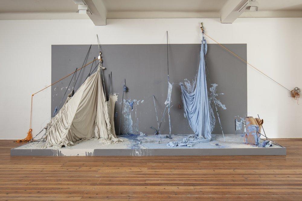 Hedvig Winge.  Leaning , 2018. Installation. Flytande porslinsmassa, textil, papper, stålstänger, rep m.m. Foto: Pär Fredin