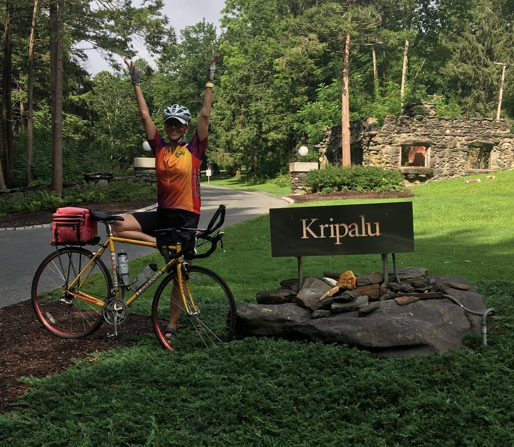 Marla strikes a yoga pose with bike at Kripalu Center for Yoga and Health