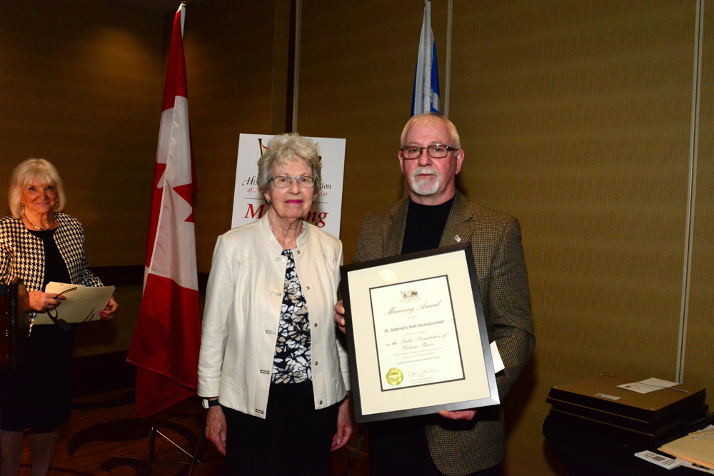 HSA Emeritus member Nancy Hickman, presents the Manning Award to John Baker, Chair of St. Gabriel's Hall Inc.