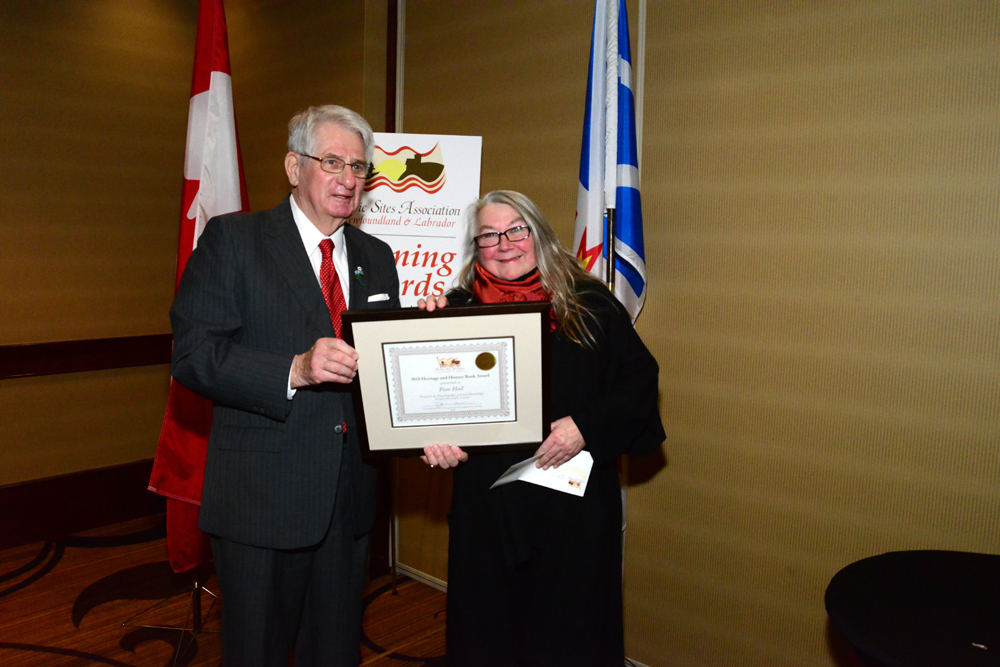 The Honourable Edward Roberts presents the 2018 Heritage History Book Award to author Pam Hall.