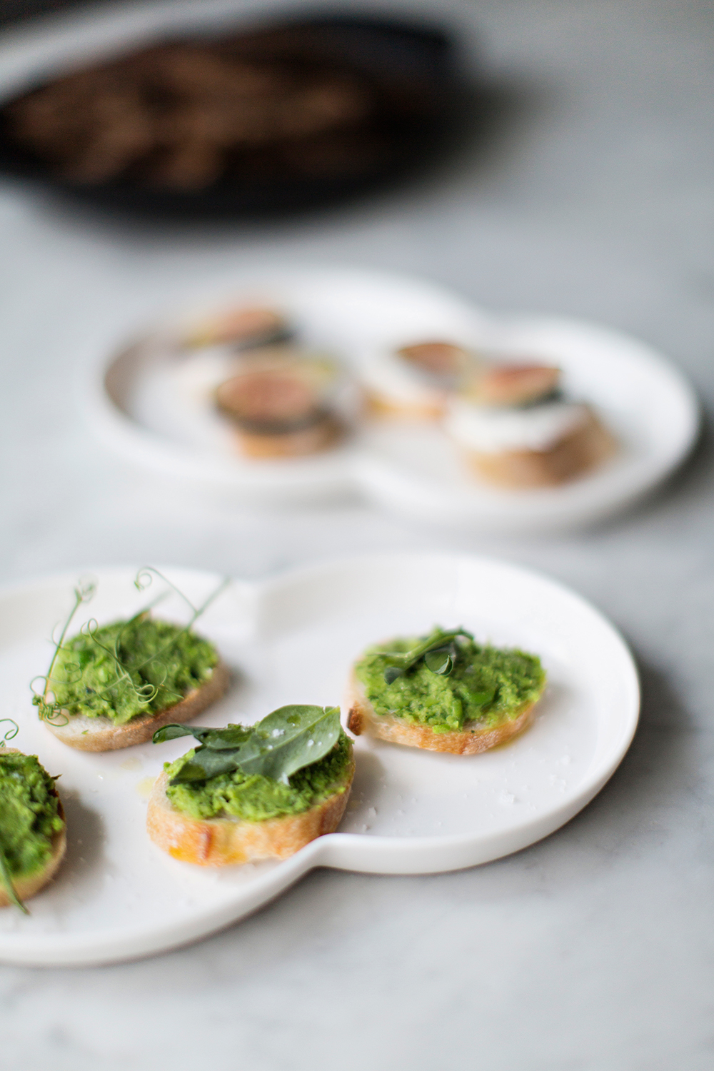 SPRING PEA CROSTINI mint + lemon 3 cups frozen peas 4 - 5 cups of water, salted 1 bunch of spring onions 1 cup fresh mint 4-5 Tablespoons of olive oil Juice of 1/2 a lemon 1 - 2 baguettes  Sea salt and pepper Pea Shoots for garnish   Fill a large bowl with ice water and set aside. In a large pot bring salted water to a boil. Add 3 cups of peas and boil for 2 minutes. drain peas in colander and place immediately in bowl of ice water to stop the cooking process. Set aside. Wash and dry the spring onions and cut them into thin slices. Sauté them in a hot pan with 1 Tbsp olive oil for a few minutes until they are soft but not browning. Wash the mint carefully and pick the leaves of the stems. Place the peas, spring onions, fresh mint, 3-4 spoons of olive oil and lemon juice in a blender and pulse until just blended. We prefer there peas to have a little texture so be careful not to over blend the puree. Season with salt, pepper and lemon to taste. If a smoother puree is desired then add a few teaspoons of olive oil until mixture is of desired consistency. Preheat the oven to 350 degrees. Cut the bread into slices 1 inch thick. Drizzle generously with olive oil and arrange on a baking sheet. Toast the bread for 3-5minutes. Remove from oven and set aside to cool. To serve, spread 1 tablespoon of puree over each slice of bread. Garnish with pea shoots and sprinkle with flaky sea salt and olive oil to taste.   Photo + Styling | Karen Mordechai Recipe | Rikke Storm