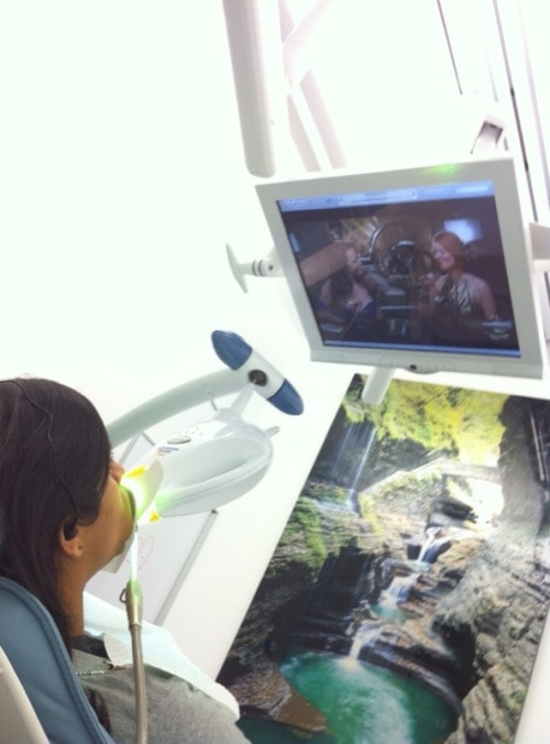 A patient watches a program while getting her teeth whitened