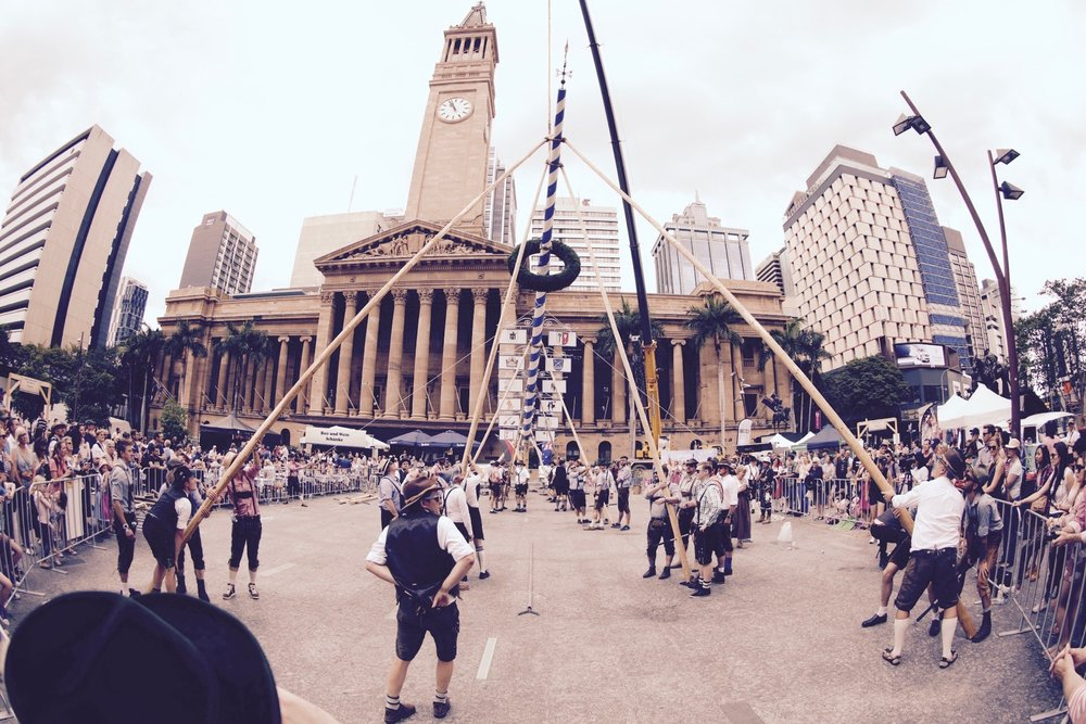 Volunteers join Bavarian visitors to help raise Australia's first 'Oktoberpole' in Brisbane