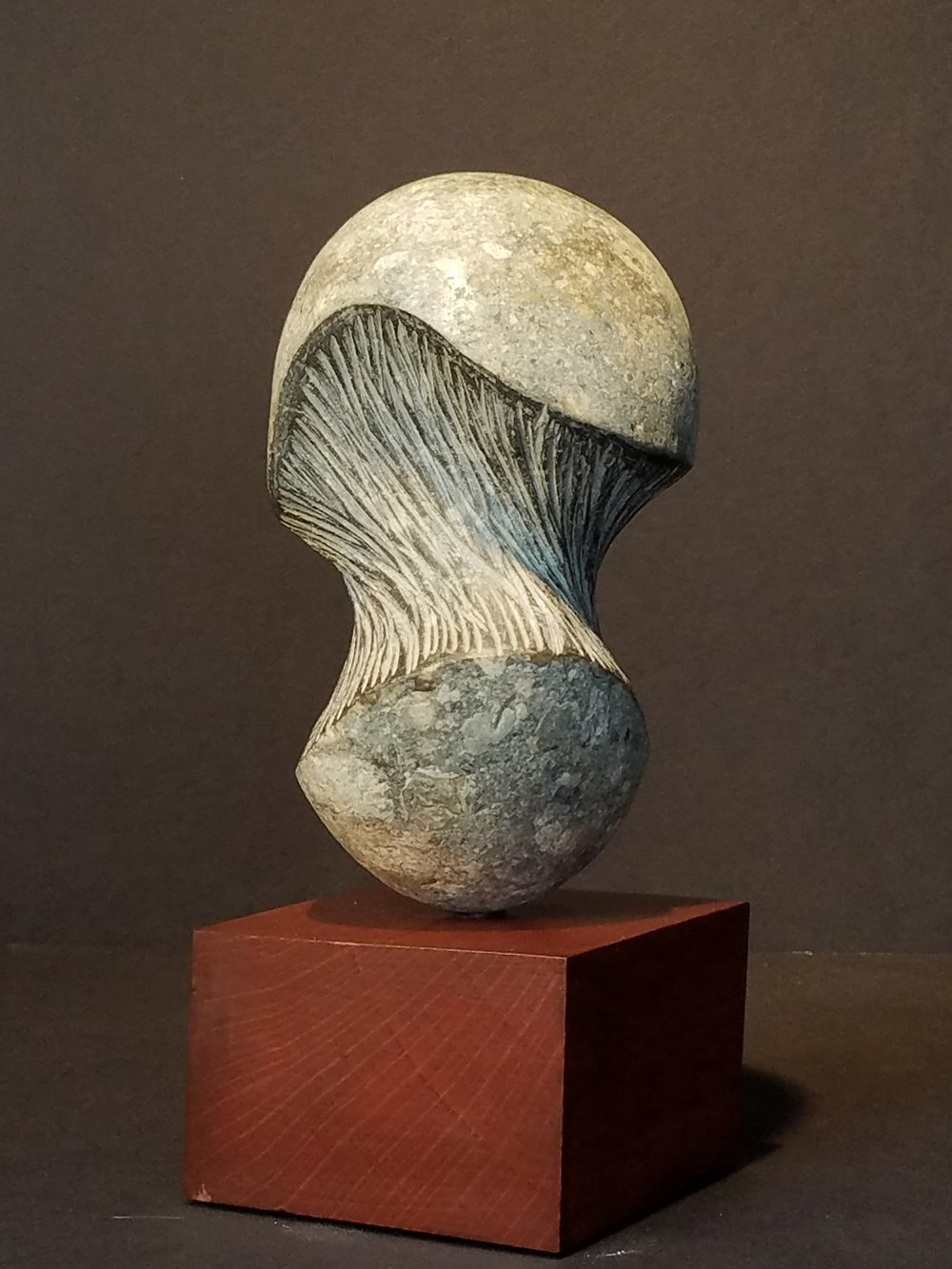 "This is from a series of works using stones found on the beach.  This piece was inspired by the existence and disappearance of the high-tech bubble at Silicon Valley in 2000.  It's an attempt to show the tension just before it bursts.  Medium: Granite on Wooden Base  Dimensions: 4-1/2"" x 4-1/2"" x 10"""