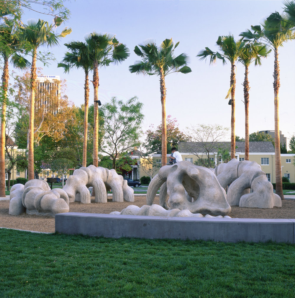 Encircled by palm trees lining the outdoor grounds of Park La Brea, a fossil-like sculpture of a saber tooth cat emerges, half-sunken, from a sandy floor.  To the passer-by and the public imagination, this skeletal sculpture injects a modern, iconic interpretation of natural history into the realm of unusual public artwork.  However contemporary its purpose may be, the sculpture's dramatically enlarged scale and dinosaur-like appearance produce a playful investigation into the prehistoric life force that once animated Los Angeles' sprawling desert basin.  Only blocks away, the La Brea tar pits - one of the most recognized fossil localities of the Earth's last Ice Age - draw crowds of thousands each year to study and learn about its peculiar geographical and geological personality.  These remarkably life-like, sculpted remains of a storybook creature bring imaginative access to La Brea's fossil excavation pits and unearth the forgotten history of a modern metropolis.  Residing at a unique juncture of the arts and recreation, and delicately integrated with its surrounding landscape, this sculpture also has a practical purpose: a children's playground and climbing structure.  While interactions with fossilized remains are typically limited to detached observation, this sculpture invites the viewer to touch, explore, and discover its disjoined features.