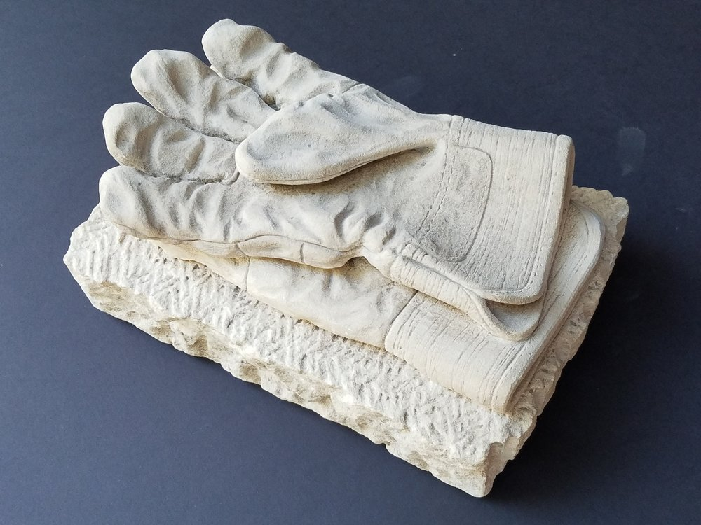 "Tribute to a basic safety device, this piece was created using my own gloves as a model. Medium: Limestone Dimensions: 17"" x 10"" x 8"""