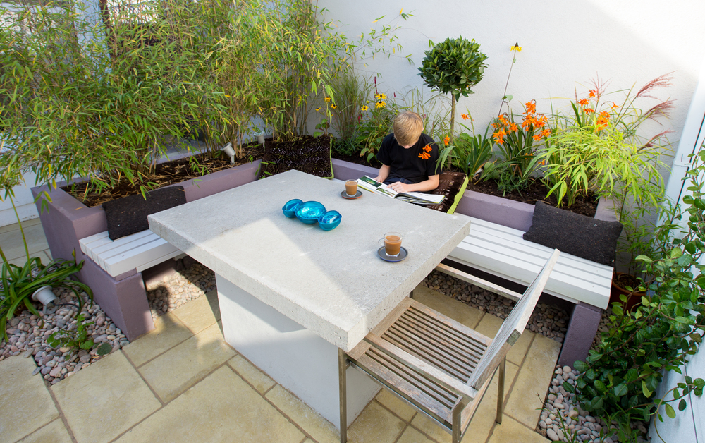 Raised planter with integrated L shaped bench seating & bespoke concrete table