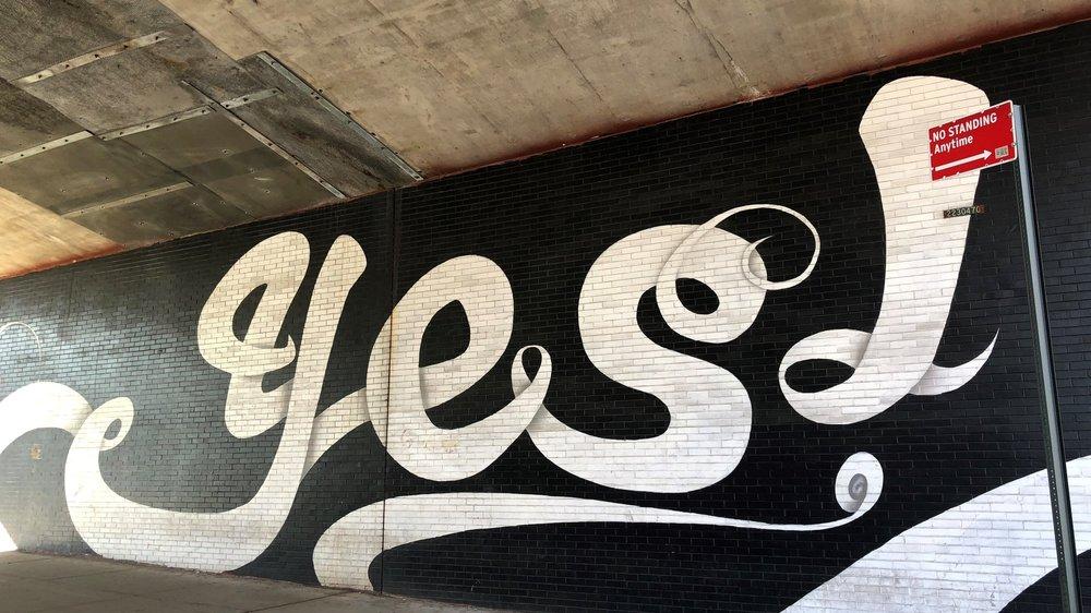 """Mehr Zufriedenheit im Beruf - schwarze Wand mit weißem Graffiti """"Yes"""""""