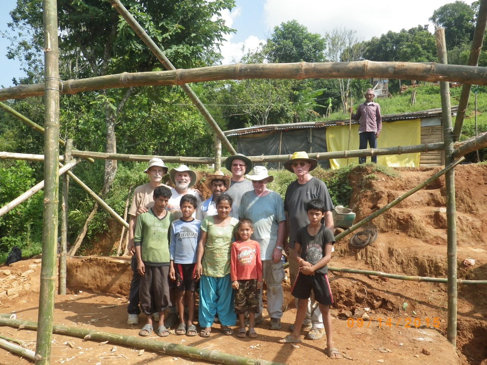 Jerry (right end of the second row) and other volunteers with the family whose house is being rebuilt.