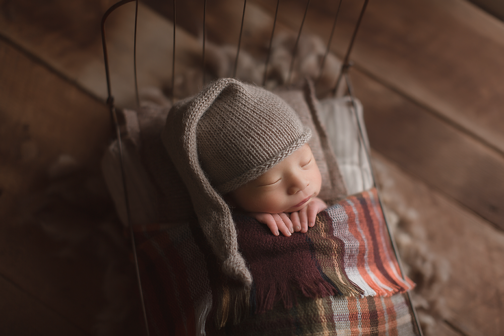 orange-county-newborn-photographer-baby-boy-in-bed-sleeping-plaid-blanket.png