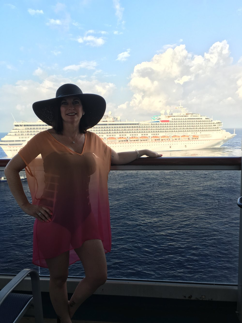 Nikki glamoursly wearing the Vivi in Fuschia Sunset Ombre Silk while cruising the Caribbean.