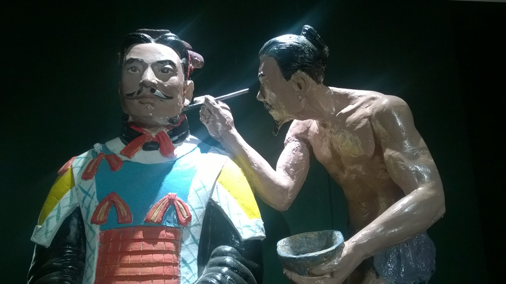 A craftsman painting the details on a Terracotta Warrior