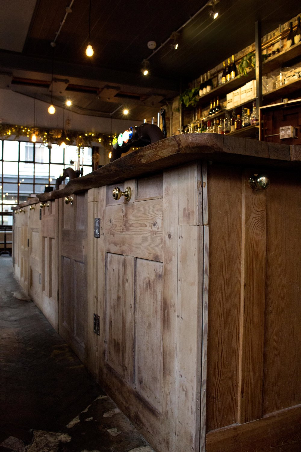 Framptons in Tunbridge Wells - The bar is made of repurposed doors with doorknobs as bar hooks - Phoebe Oldrey Interior Design.jpg