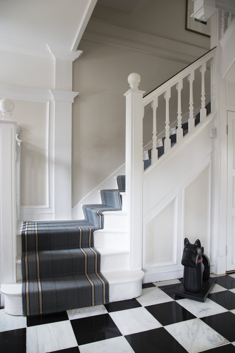 Black and white tiling and a blue stair runner in a classic contemporary home full of period features in Sevenoaks Kent - Interior Design by Phoebe Oldrey of Smartstyle Interiors