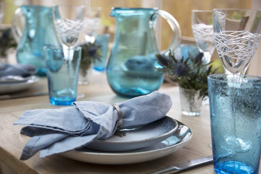 A wooden table is set with turquoise glassware and blue table linens and plates from West Elm in a kitchen extension in Sevenoaks Kent - Interior Design by Phoebe Oldrey of Smartstyle Interiors.jpg
