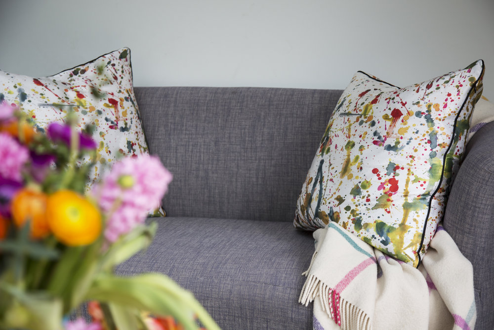 Colourful cushions from Habitat pop against a grey sofa in an arts and crafts family home in Sevenoaks Kent - Interior Design by Phoebe Oldrey of Smartstyle Interiors