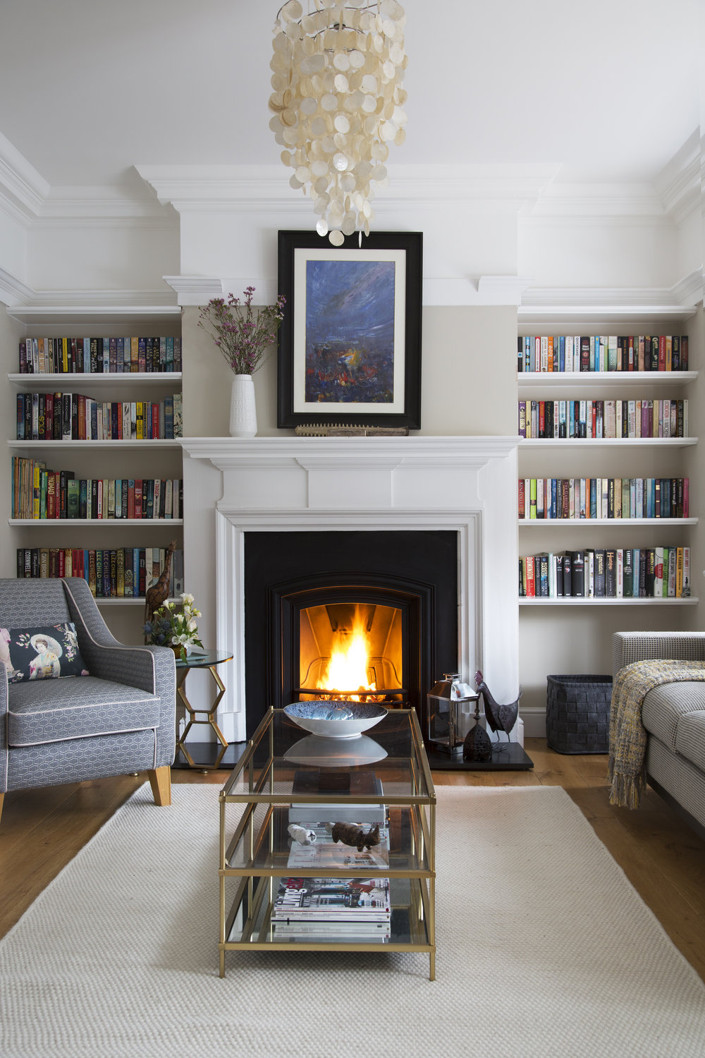 Period features and an open fireplace with contemporary pieces like a brass coffee table in an arts and crafts family home in Sevenoaks Kent - Interior Design by Phoebe Oldrey of Smartstyle Interiors