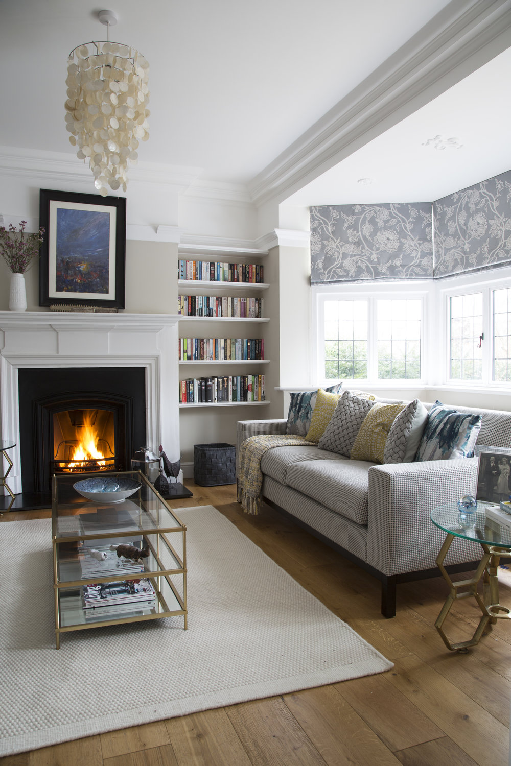 A brass coffee table and modern grey sofa compliment an open fireplace and period features in this family home in Sevenoaks Kent - Interior Design by Phoebe Oldrey of Smartstyle Interiors