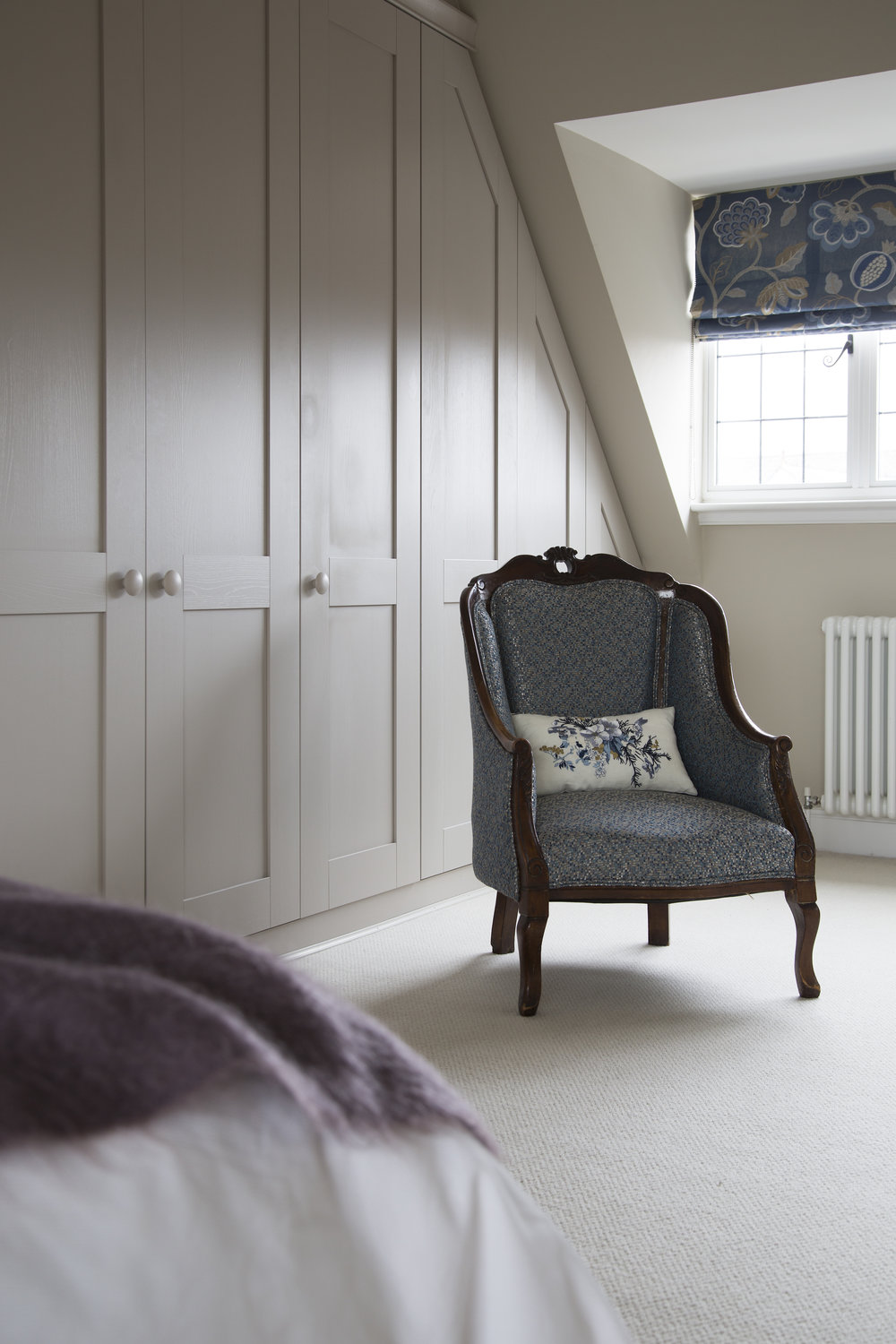 An upholstered sitting chair and bespoke roman curtain in a classic contemporary bedroom in Sevenoaks Kent - Interior Design by Phoebe Oldrey of Smartstyle Interiors