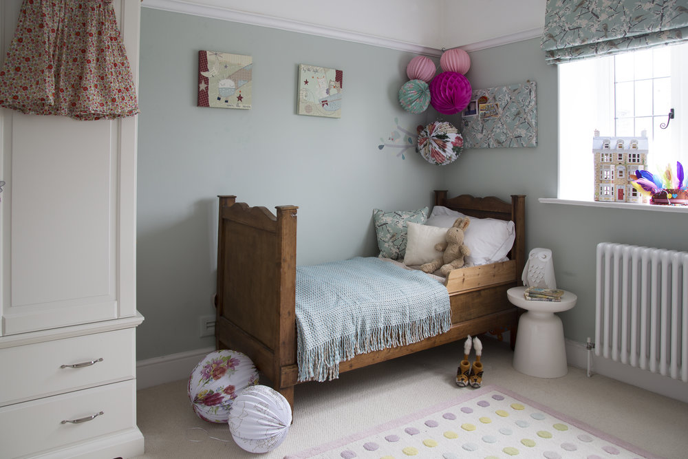 A little girl's bedroom in Sevenoaks Kent is filled with colourful paper pom-poms and charming details for a classic contemporary look - Interior Design by Phoebe Oldrey of Smartstyle Interiors