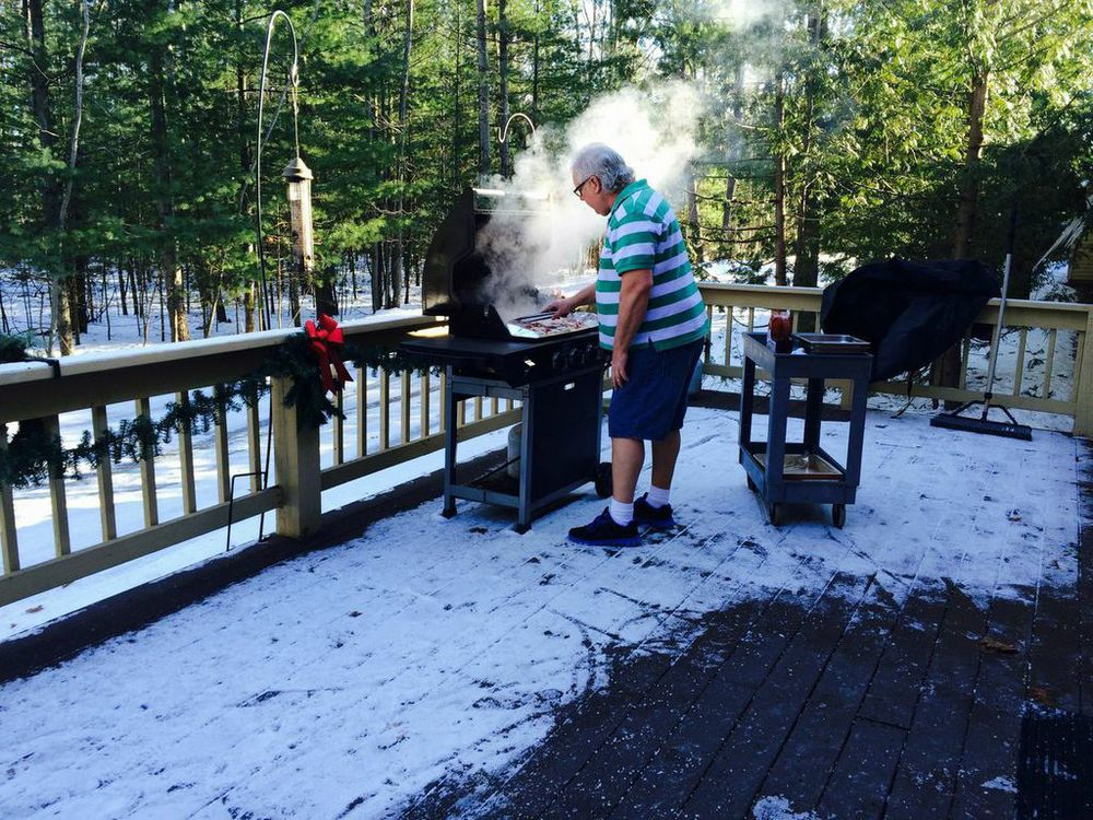 CHEF DEAN TAKES ADVANTAGE OF A SUNNY WINTER DAY TO PREPARE GRILLED CHICKEN FOR OUR RESIDENTS.