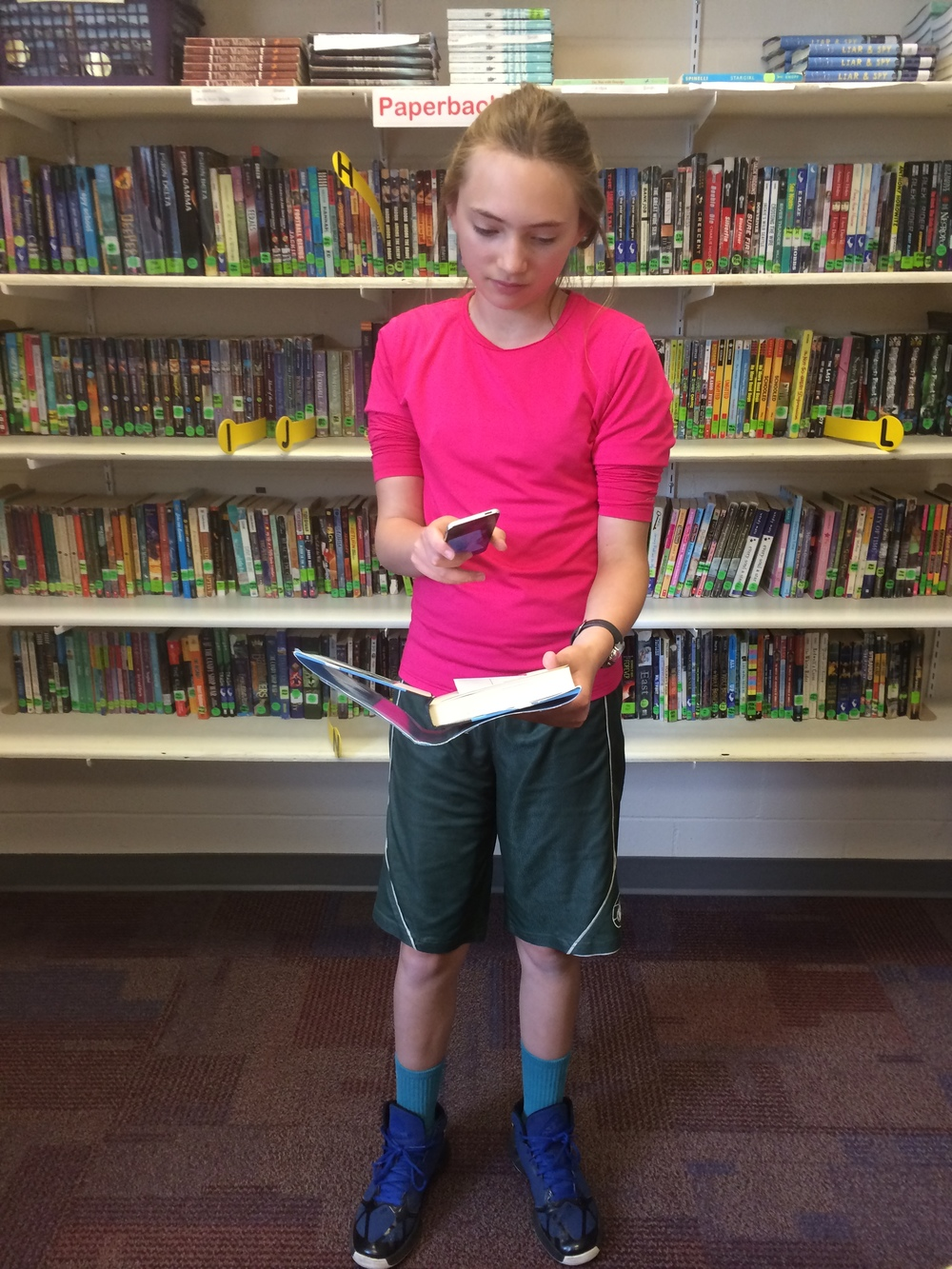 A student scans the QR code in a library book.