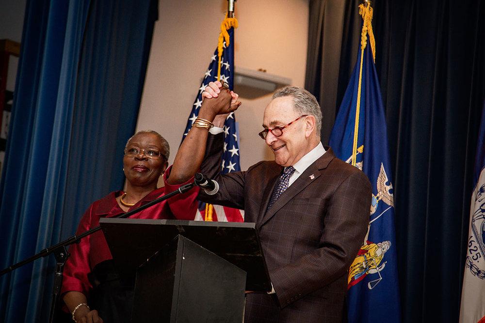 Senator Brian Benjamin's mother is joined by U.S. Senator Chuck Schumer.